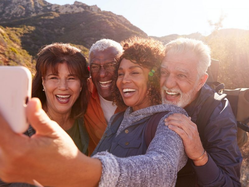 Group Of Senior Friends Posing For Selfie As They Hike Along Trail In Countryside Together